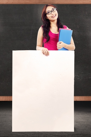 Female teacher holding empty copy space in front of chalkboard photo