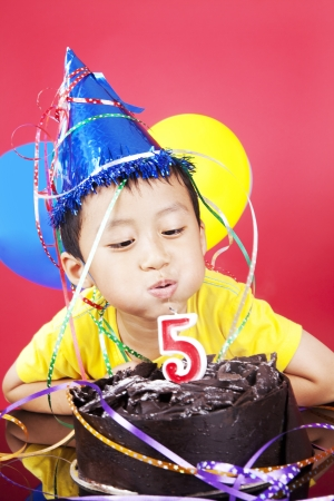Cute asian boy blowing fifth candle birthday at his birthday party, shot in studio photo