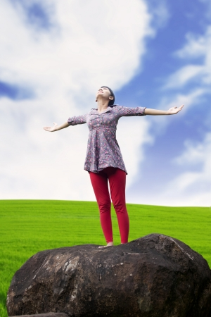 Young girl spreading hands with joy and inspiration facing the sky Stock Photo - 14684384