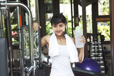 Friendly fitness young woman holding a bottle of water and smiling at the gym photo