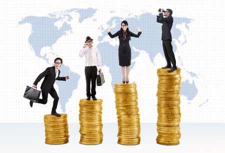 Business success concept: Businessmen and businesswoman standing on stacks of golden coins photo