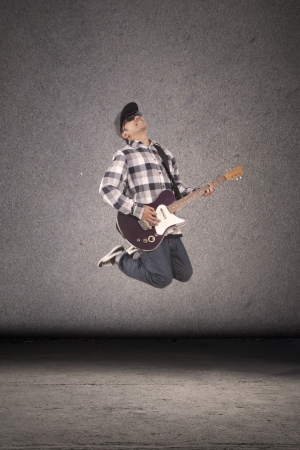 Young guitar player perform at street jumping in front of dark bakground photo