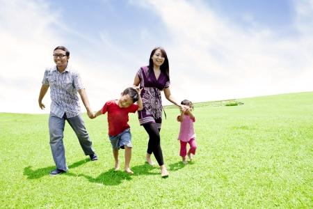 Familia feliz asi�tica runing juntos en prado tiro al aire libre photo