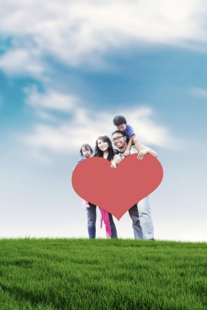 Happy Asian family carrying a big heart cutout with copy space. Shot in meadow during summer