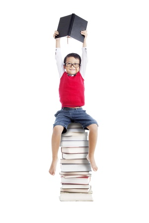 Portrait of asian schoolboy holding a book and sitting on a stack of books isolated on white Stock Photo