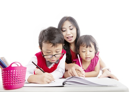 Portrait of young asian mother guiding her children to draw on the paper Stock Photo - 14684281