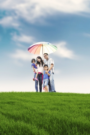 child protection: Happy family with parents and two kids posing in meadow. Father carrying an umbrella symbolizing protection for the whole family.