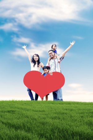 Happy Asian family carrying a heart cutout with copy space in meadow.  photo