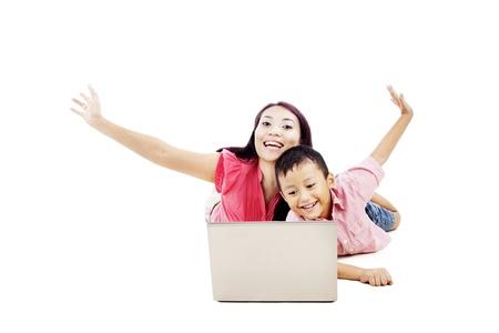Aantrekkelijke gelukkige moeder met haar zoon glimlachen en poseren met laptop computer. geschoten in de studio Stockfoto