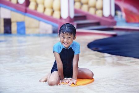 Cute Asian kid having a good time at swimming pool photo