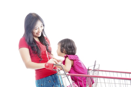 Portrait of happy asian mother laughing with her daughter on the shopping cart  Isolated on white photo
