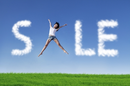Asian woman jumping make the word sale photo