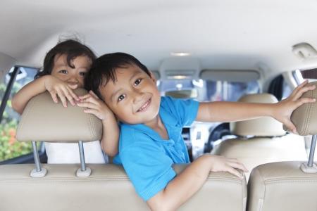 Glimlachend gelukkig broers en zussen speels in de auto Stockfoto