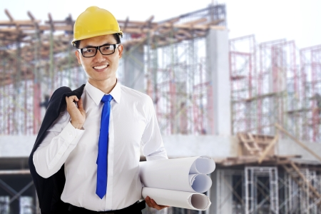 Happy smiling engineer holding a blueprint shot at workplace outdoor Stock Photo - 14684331
