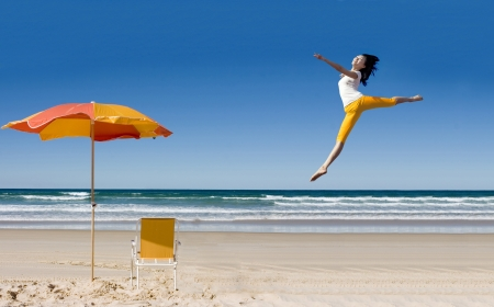 leap: Happy asian woman jumping at tropical beach expressing her freedom Stock Photo