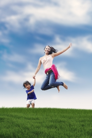 Happy asian woman jumping with her daughter shot outdoor