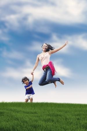Mujer feliz asiático saltando con su hija disparó al aire libre