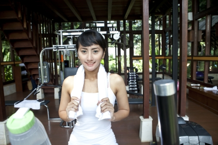 Healthy Asian woman smiling with towel in home gym photo