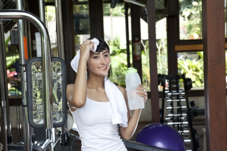 Beautiful asian woman posing with towel and bottle of water in a gym photo