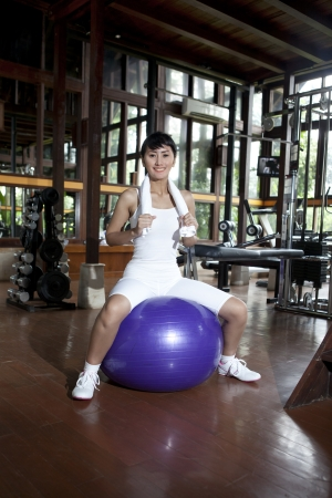 Healthy Asian Woman posing with Swiss Ball in a fitness club photo