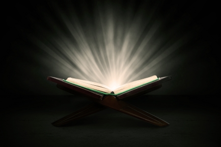 stories: Muslim holy book of koran shot in studio on dark background, with shiny rays
