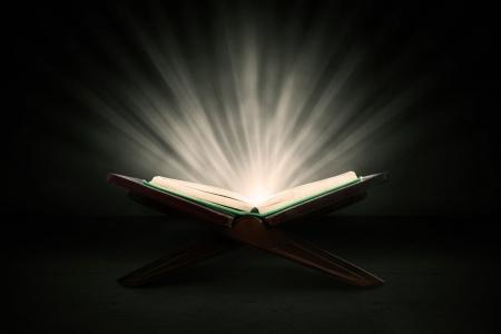 destin: Musulmane livre sacr� du Coran tourn� en studio sur fond sombre, avec des rayons brillants Banque d'images