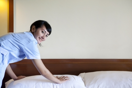 hotel worker: Beautiful Asian maid making bed in hotel room. Copy space available for your text