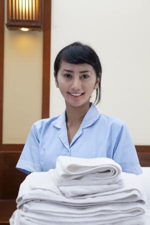 ama de llaves: Se�ora sonriente joven con toallas de limpieza en una habitaci�n de hotel
