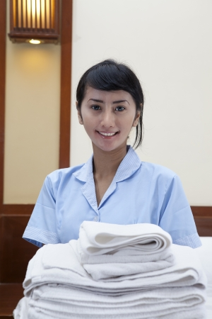 Smiling young cleaning lady holding towels in a hotel room  Stock Photo - 14684433