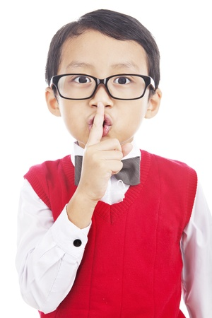 Cute asian elementary school student with his finger over her mouth, hushing. photo