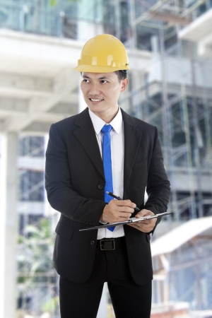 An engineer on construction site checks details on a clipboard.  Stock Photo - 14684376