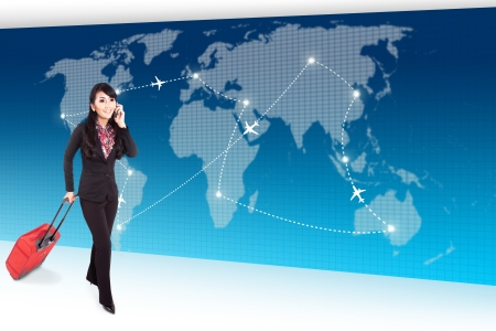 Businesswoman carrying suitcase and talking on the phone walks in front of global transportation map photo
