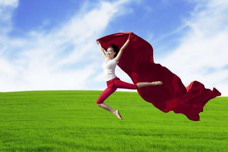 Young asian woman jumping with red scarf shot at meadow photo