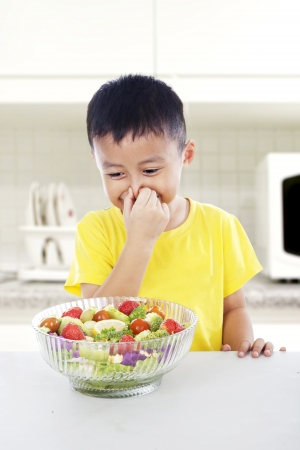 That smells bad! Young asian child covering his nose from vegetables. shot in kitchen photo