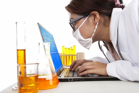 Lab assistant woman works with laptop and test-tubes in laboratory photo