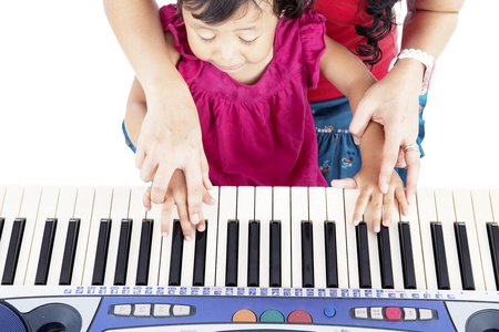 Portrait of asian little girl playing piano with her mother guiding her hands photo