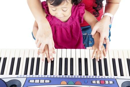 tocando el piano: Retrato de ni�a asi�tico tocando el piano con su madre, guiando sus manos Foto de archivo