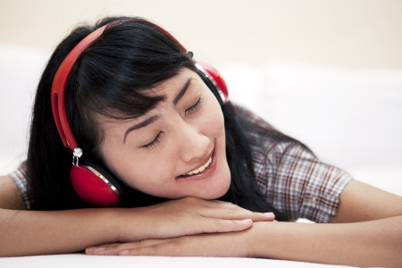Cute Asian woman with a headphones listening to a music in a bedroom  photo