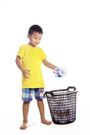 cesto basura: Responsabilidad del niño pequeño para mantener el medio ambiente limpio por tirar residuos de papel a la papelera de reciclaje