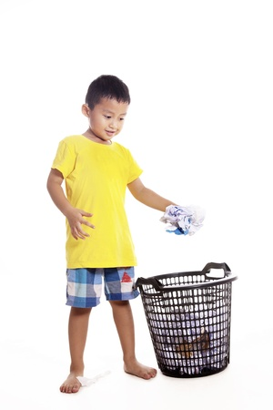 Responsibility of young little boy to keep clean environment by throwing waste paper to recycle bin photo
