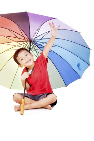 Shot of cute asian boy smiling under multicolored umbrella photo