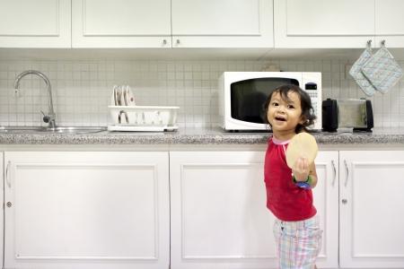 microondas: Ni�a linda que sostiene un pan en la cocina. un disparo en la cocina con un interior moderno
