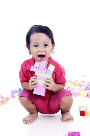 Laughing little girl playing with colorful blocks, isolated on white background  photo