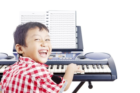 keyboard keys: Portrait of little piano player smiling and playing the piano. shot in studio isolated on white