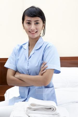 Pretty maid woman posing in hotel bedroom
