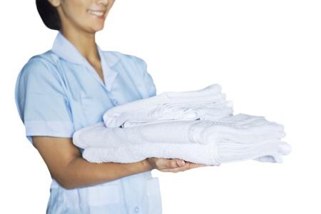 empleada domestica: Maid mujer sosteniendo toallas. Tirado en el estudio aislado en el fondo blanco