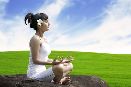 lotus pose: Young asian woman doing yoga exercise on a stone