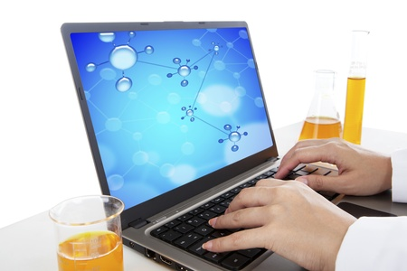 Hands typing on laptop computer doing an experiment of chemical molecule photo