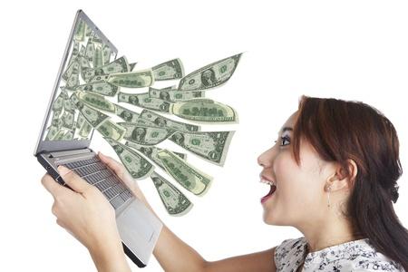 loteria: Mujer joven con ordenador portátil y dinero en un gran negocio on-line