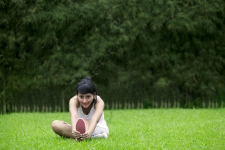 Beautiful woman doing stretching exercise on green grass at park Stock Photo - 14684451